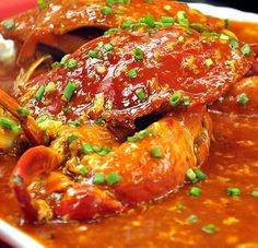 Chili Crab Recipe - the unofficial national dish of Singapore.  This simple dish with unbelievable flavor is mouthwatering, lip burning, and soul invigoration goodness will leave you wishing you could reverse time to eat it again.........from marcussamuelsson.com