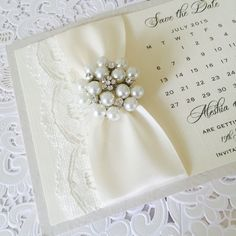 Luxury Save the Date calendar card styled with lace and vintage brooch. This beautiful save the date card is designed on thick board card to give the look of luxury. Printed on ivory 300gsm linen card and mounted onto an ivory embossed card. £3.80 each with envelopes from www.amordesigns.co.uk