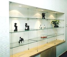 Wire cable suspended thick glass shelves in front of onyx