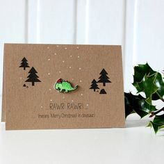 Did you know? 'RAWR RAWR!' means 'Merry Christmas' in dinosaur! Say a very Merry Christmas to your friends and family with this cute dinosaur Christmas card!Handmade in Scotland using recycled card, this brilliant Christmas greetings card features a hand drawn plastic dinosaur, all dressed up in his Santa hat! Inside is a fitted liner insert which has been left blank for you to write your own message, and each card comes complete with a co-ordinating white envelope, all sealed tightly in a…