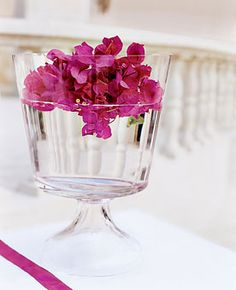 Brides.com: . Miss Manila bougainvillea floating in a clear hand-blown footed bowl, from DK Living,  845/265-6080, adds a burst of color to the ceremony setting.