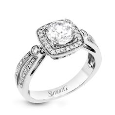 This wonderful 18k white gold ring has a distinctive design with a soft square halo and .34 ctw of white diamonds.