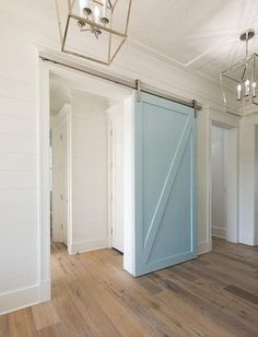 White shiplap walls frame a powder blue barn door on a silver rail illuminated by Darlana Medium Lanterns hung from a white plank ceiling over sawn oak wood floors.