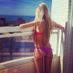 #blonde in red #bikini and purple undies looking out of balcony onto water