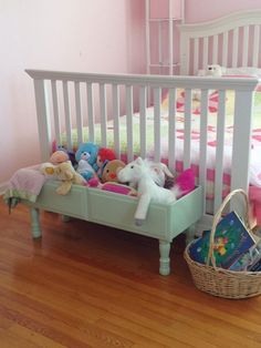 Re purposed dresser drawer, add legs to create child's toy storage at the end of bed. Such a great idea.