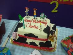 Semi-DIY Woody/Jessie-Inspired Cake.   A grocery store 1/8 sheet cake stacked on top of a 1/4 sheet cake.  Have them stack it & ice it with NO decoration. Get black Wilton Sugar Sheets & cut in random cow-print pieces & place on cake.  Cover seams with bandana ribbon.  Use store-bought figurines (I got ours from the Disney store). #toystory #birthdaycake