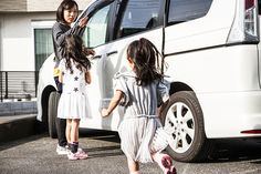 Mother and two sisters are coming to a car. Mother is beckoning to little sister. Little sister is running to her mother and elder sister standing by a car.
