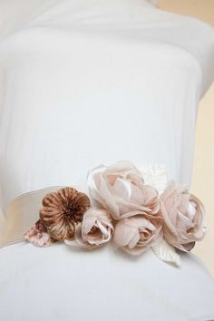 This bridal sash is made with 4 beige and cream organza, chiffon, polyester fabric handmade rose flowers and decorated with beige lace. Decorated