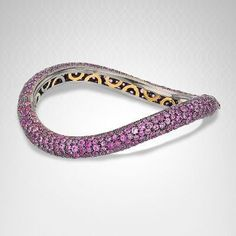 Salavetti Pink Sapphire Bangle in 18K Gold and Sterling Silver - Hundreds of pink sapphires shine in this uniquely curved bangle. Part of the Salavetti collection, this gorgeous bangle is sure to be a show stopper. It is nicely set in 18k gold and sterling silver.