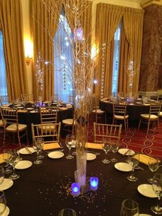 DIY wedding centrepieces Hire vases Bought gold branches Blue Voltive hire  Black linen hire Gold Chiavari Chairs - Gold Star Venue London