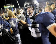Utah State safety McKade Brady celebrates with fans after the Aggies defeated Utah 27-20 in overtime, Friday, Sept. 7, 2012, in Logan