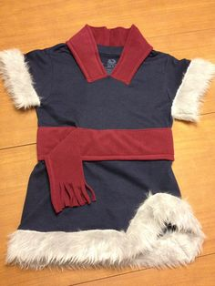 DIY Christof costume created from a boys t-shirt, woman's polar tech scarf (used for belt) and ear band (used for neck trim), and 1/4 yard fur fabric. Cut sleeves off t-shirt at angle and attach fur. Cut small v in neck of t-shirt then cut one side of ear band and attach to neckline of t-shirt.  Attach scarf as belt and make v shape cut on lower right of t-shirt and attach fur. Pairing with a long sleeve blue shirt and grey pants and we are ready for the Frozen themed birthday party.