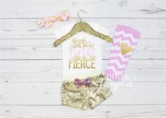 This gorgeous Pink and Gold Birthday outfit is the perfect way to dress up your little one for her special day. Though She be Little She is ONE is in the sparkliest of gold glitter and matte light pink. Glitter is high quality and doesnt flake or shed off! SS= Short Sleeve bodysuit LS=Long Sleeve Bodysuit. COMPLETE 4 Piece Set (as pictured) Includes: ♥ 1 Onesie ♥ 1 Pink and Gold Knot Headband. ♥ Gold Sequin Shorts with removable Pink Sequin Bow ♥ Set of Pink and White striped legw...