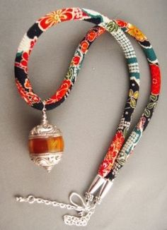 New work... Kimono cord with Nepalese resin and silver focal bead; silver closures and cones...