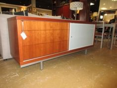 : $1199.99 | Item #: 89124  Calligaris cabinet in a medium tone with a sliding glass door. There are three touch latch drawers down one side of this cabinet. There is also a media hole cutout behind the glass door, so you can use this as a TV console or a buffet in your dining room...