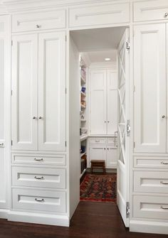 Amazing hidden walk-in pantry with white kitchen cabinets flanking secret mirrored pantry door.