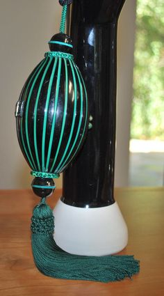 1920s art deco oblong shaped dance purse in green and black with sparkling green rhinestone accents on the top and bottom. The purse opens and closes without any difficulty and retains the original silk pocket and mirror. Measures 16 inches from top of rope handle to bottom of tassel.