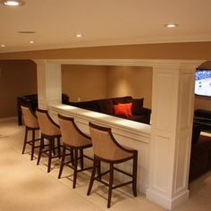 Basement entertaining.  By opening up the support wall with counter & stools behind the sofa this visual opening gives the room a larger feel and allow for a bigger crowd.  Note: lighting above the counter is key.