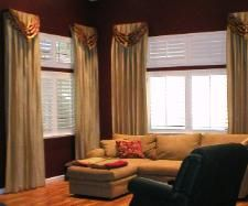 The custom drapery panels with a scarf swag are set off well by a backdrop of deep red walls.