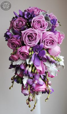 Trailing bouquet of roses, orchids and freesia.....use ranunculus in color with blue freesia instead of the purple