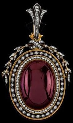 An antique diamond rhomb and garnet pendant, French, circa 1900. Mounted in gold with a compartment on the reverse. French assay mark.