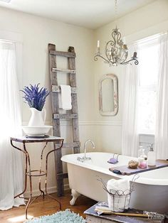Outfit your bathroom with old things that bring new purpose. Here, a handcrafted ladder doubles as a towel rack, and a rusty table and worn bench provide display and resting spots for bathing necessities. Check out the wooden tray that spans the tub; the handy solution keeps lotions and scrubs in easy reach.