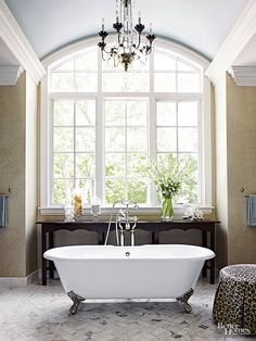 This chandelier's painted wood base, black metal details, and chic silhouette complement this elegant bathroom design.