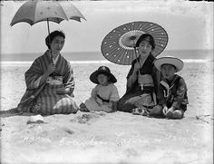 Japan 1920s. Family at the beach. Kimonos and a sailor suit. Umbrella and parasol.