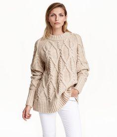 Hellbeige. Weicher Zopfstrickpullover mit Wollanteil. Der Pullover hat lange Raglanärmel und eine weite Passform. Rippenbündchen an Hals, Ärmelabschlüssen