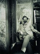 "Alphonse Mucha:  Sitting in front of ""Gismonda,"" which brought him immediate fame when, in December 1894, he accepted a commission to create a poster for Sarah Bernhardt."