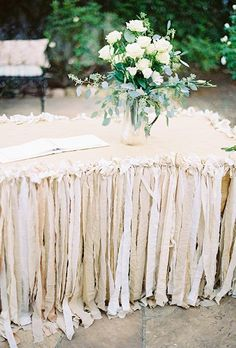 Dress up your guestbook station with strips of linen to create a fanciful fringe table skirt | Brides.com