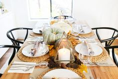 Traditional Thanksgiving tablescape with geometric candleholders, woven placemats, and natural elements including pumpkins, pinecones, and celebratory crackers.