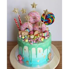 A MASSIVE Vanilla Ombré Cake  (strawberry coulis and fresh vanilla buttercream between four teal ombré layers of vanilla sponge, topped with a white chocolate ganache, doughnuts, rock, strawberry macarons, moam pinballs, jelly beans, ferraro rochers, custard creams, oreos, sour belts, gold leaf, and sprinkles) ⭐️ #cake #vanillacake #ombrecake #dessert #foodporn #cakesofinstagram #dripcake #celebrationcake #birthdaycake #glasgow #glasgowcakes #lilybakescakes #macaron #foodie #cakesbae #fe