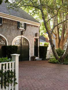 The brick driveway, carriage house doors, shingle siding and lanterns bring soft touches to this exterior. Door Design, Exterior Design, House Design, Garage Design, Future House, Brick Driveway, Cobblestone Driveway, Garage Door Styles, Shingle Siding