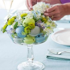 An easy Easter centerpiece featuring colorful Easter eggs, green blooms and a lovely glass.