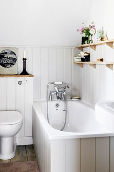 All-white bathroom with wood shelves above bathtub