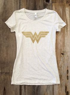 This glittery gold Wonder Woman print is in an oatmeal triblend Bella brand tshirt.