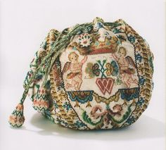 An eighteenth-century French bridal bag; stitched with symbols of love: two conjoined hearts flanked by a pair of putti holding a crown. (anilau.buzznet.com)