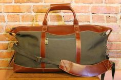 Canvas and Leather men's travel bag.  Made with forest green canvas and buffalo hide leather Padded shoulder strap Matching leather luggage tag Plaid interior