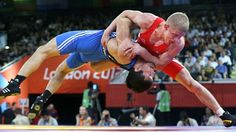 Lithuania's Edgaras Venckaitis is lifted off the mat by Kazakhstan's Darkhan Bayakhmetov (in blue) during their match in 66-kg Greco-Roman wrestling