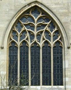 This window is uniform in style and the theme is distinctly botanical. The tracery under each sub-arch resembles a plant with three giant leaves growing from a stalk formed by one of the mullions.