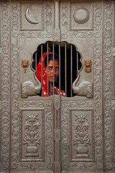 Gypsy girl behind a door, Pushkar, Rajasthan, India.
