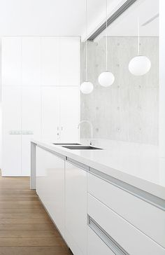 Wrap-around counter - minimal white kitchen - sleek cabinets - contemporary