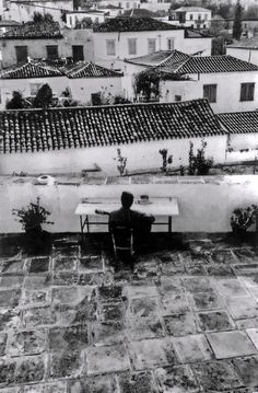 Leonard Cohen playing guitar on the terrace of his house on Hydra. Greece 1982 by Dominique Issermann.
