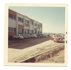 O Edifício I, o estacionamento ainda em terra, e, ao menos, 9 automóveis Marca Volks-Wagen, Modelo Fusca, estacionados.