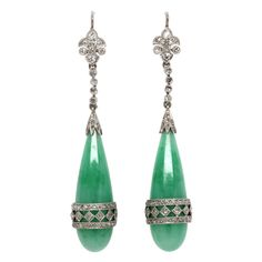 18K white gold, wire back earrings set with rose cut diamonds in a fleur de lis design followed by bezel set diamonds holding a long burmese jadeite teardrop banded with 2 rows of diamonds spaced by diamond set oblique squares approx 1.00ct total weight. 2+ inches long. Beautiful dramatic look