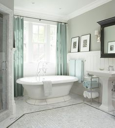 White + gray bathroom with light blue curtains and towels.
