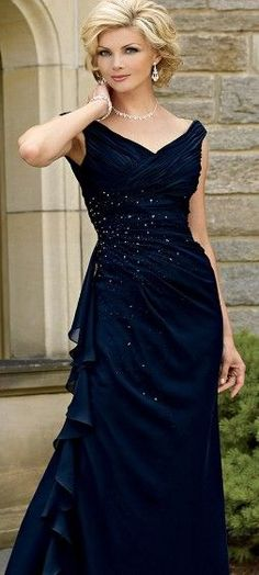 A long Formal Gown with v neck line for the mother of the bride. This lightly ruched navy blue evening gown is slanted to one side where there is a chiffon scarf hanging down for added drama. There are sparsely dense crystals sprayed over the dark blue evening dress. To see other sleeveless mother of the bride dresses for inspiration you can visit www.dariuscordell.com ( we offer custom evening dresses as well as replicas of haute couture gowns at an affordable price)