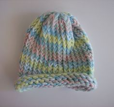 Loom knit baby hat using two strands of Caron baby print one pound yarn.