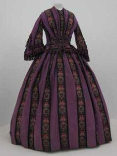 (ca. 1860) Cette robe est faite autour de 1860 et se compose de soie pourpre avec de larges emplois tissés en noir, vert et blanc avec motif de fleurs et cachemire. Le modèle a un corsage ajusté avec une jupe. Les manches sont également largement une frange de soie.